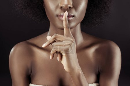 cropped shot of african american woman showing silence gesture isolated on black