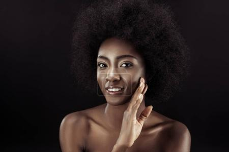 beautiful african american woman touching her face isolated on black