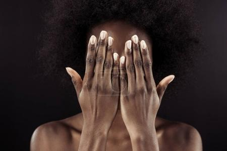 african american woman covering face with hands isolated on black