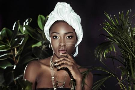 young african american woman in white wire head wrap behind leaves looking at camera
