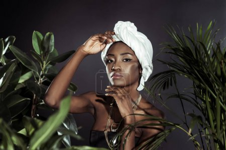 fashionable african american woman in white wire head wrap behind leaves
