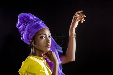 Photo pour Vue de côté de la jeune femme afro-américaine dans des vêtements vintage élégant isolé sur noir - image libre de droit
