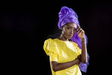 attractive african american woman in purple wire head wrap clothing isolated on black