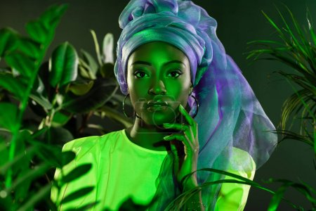 Photo for Attractive african american woman in traditional wire head wrap under green light behind leaves - Royalty Free Image