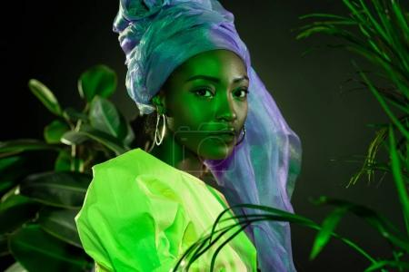 stylish african american woman in traditional wire head wrap under green light behind leaves