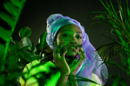 Photo for Sensual african american woman in traditional wire head wrap under green light - Royalty Free Image