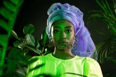 young african american woman in traditional wire head wrap under green light looking at camera