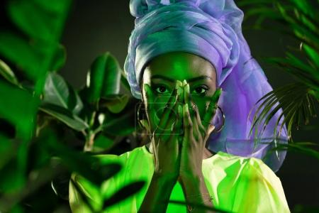 young african american woman in traditional wire head wrap covering face with hands under green light