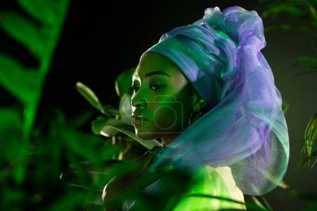 attractive african american woman in wire head wrap under green light behind leaves