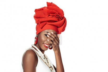 young african american woman in wire head wrap covering face with hand isolated on white
