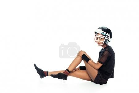 side view of female american football player in equipment resting on floor isolated on white