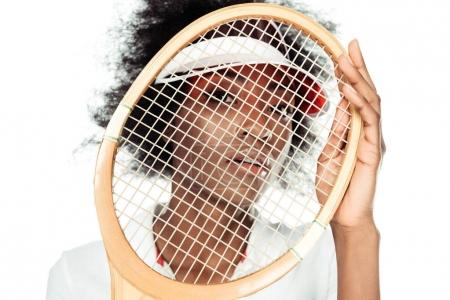 close-up portrait of young female tennis player holding racket in front of face isolated on white