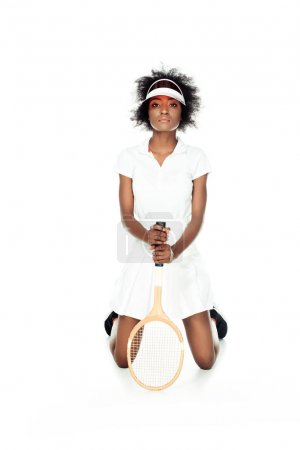 serious female tennis player with racket standing on knees isolated on white