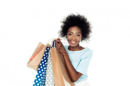 Photo for Smiling young woman holding various shopping bags isolated on white - Royalty Free Image