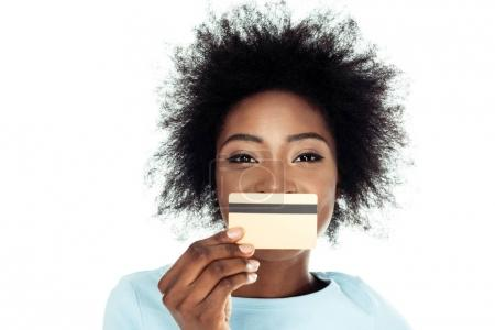 young woman holding gold credit card in front of face isolated on white