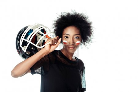 attractive female american football player with painted face holding helmet isolated on white