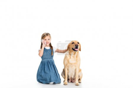 Foto de Adorable kid sitting with dog while talking on smartphone, isolated on white - Imagen libre de derechos