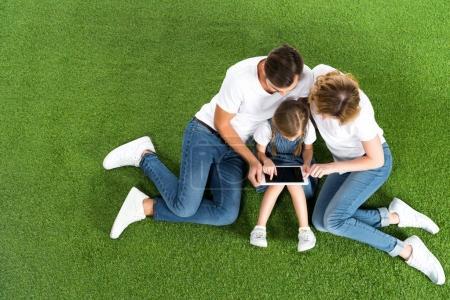 Photo pour Vue aérienne de famille à l'aide de tablette numérique tout en étant assis sur l'herbe verte - image libre de droit