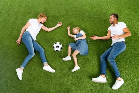 overhead view of family playing soccer together on green lawn