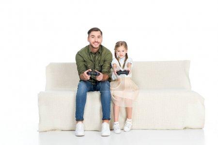 Foto de Sonrisa de padre e hija jugando videojuegos juntos aislado en blanco - Imagen libre de derechos