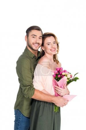 Photo pour Homme souriant étreignant femme avec bouquet de fleurs et carte postale isolé sur blanc - image libre de droit