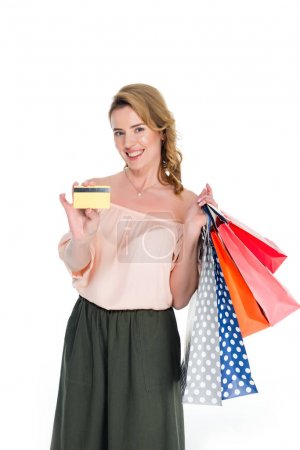 smiling woman with shopping bags showing credit card in hand isolated on white