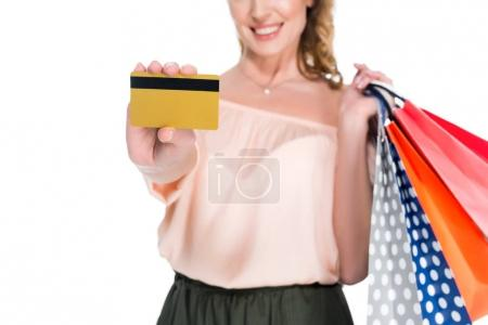 partial view of smiling woman with shopping bags showing credit card in hand isolated on white