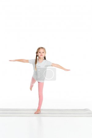 cute child practicing yoga on yoga mat isolated on white