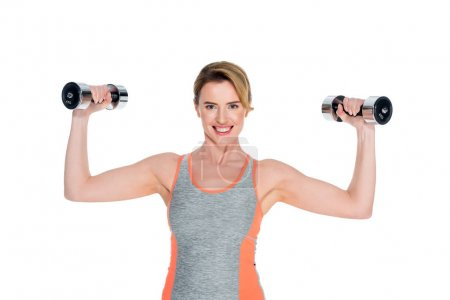 portrait of smiling woman in sportswear exercising with dumbbells isolated on white