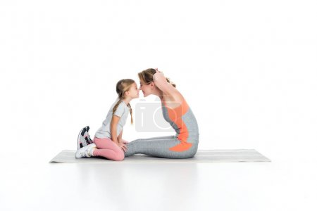 Photo for Sportive mother and daughter exercising together isolated on white - Royalty Free Image