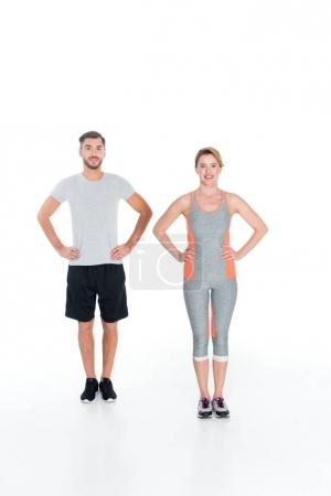 smiling couple in sportswear standing akimbo isolated on white