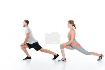 side view of sportive couple warming up before training isolated on white