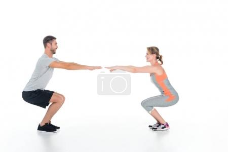 athletic couple in sportswear doing sit ups isolated on white