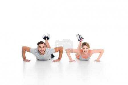cheerful athletic couple doing push ups together isolated on white
