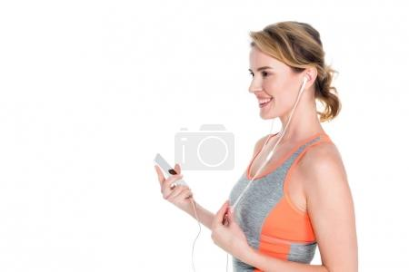 smiling woman in sportswear listening music in earphones isolated on white