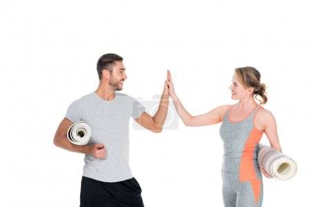 athletic couple with yoga mats giving five to each other isolated on white
