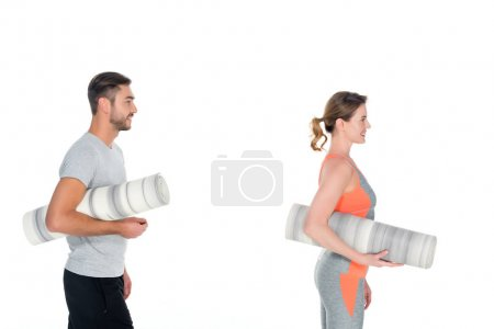 side view of athletic couple with yoga mats isolated on white