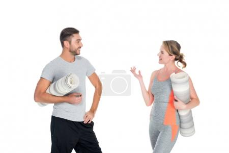 portrait of athletic couple with yoga mats having conversation isolated on white