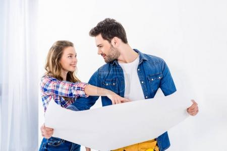 smiling girlfriend pointing on blueprint to boyfriend