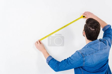Photo for Rear view of man measuring wall with tape measure on white - Royalty Free Image