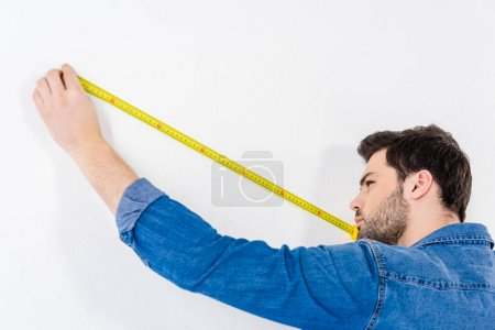Photo for Man measuring wall with tape measure on white - Royalty Free Image