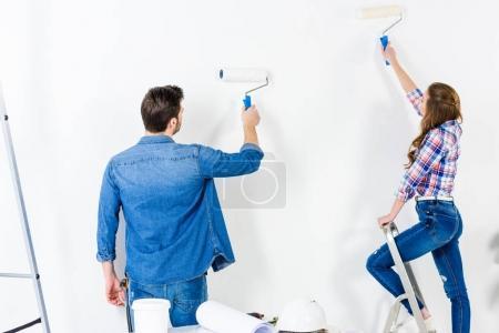 vista trasera de la pared de pintura de pareja con pintura blanca