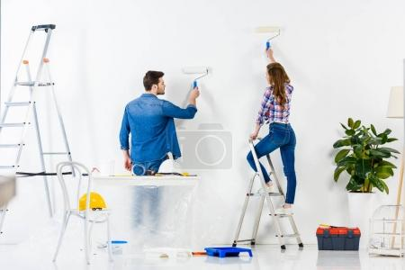 rear view of couple painting wall with white paint