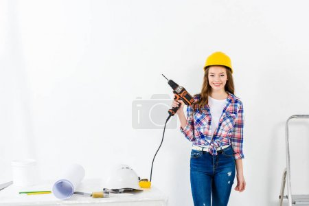 young woman holding drill and looking at camera