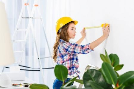 young woman measuring wall with tape measure