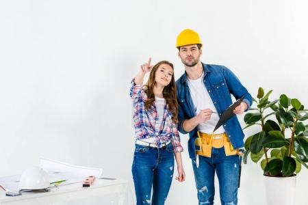 apartment owner pointing on something to worker