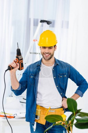 smiling handsome man standing with drill and looking at camera
