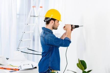 Photo pour Vue latérale de bel homme en utilisant la perceuse et faire des réparations - image libre de droit