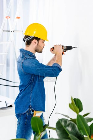 side view of handsome man using drill and making repairs