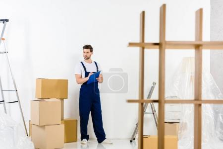 handsome relocation service worker standing with clipboard